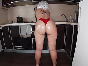Mommy stands in the kitchen in a thong and fantasies of anal sex